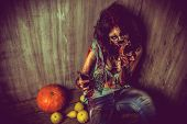 picture of bloody  - Terrible bloody zombie girl sitting by the old wall and pumpkins - JPG