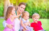 picture of mother baby nature  - Portrait of happy mother with cute little babies sitting on fresh green grass field - JPG