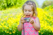 stock photo of shoot out  - Little girl amazed by pictures on point and shoot camera - JPG