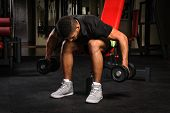 pic of bent over  - handsome young african descent mixed race man doing Seated Bent Over Dumbbell Reverse Fly workout in gym - JPG