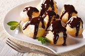 stock photo of cream puff  - Delicious profiteroles with cream and chocolate glaze on a plate - JPG