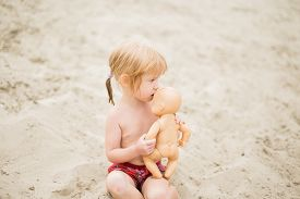 pic of baby doll  - Cute toddler girl with red hair at the beach kissing her baby doll - JPG