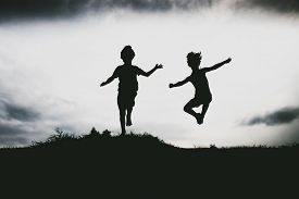 foto of children beach  - Silhouettes of kids jumping from a sand cliff at the beach - JPG