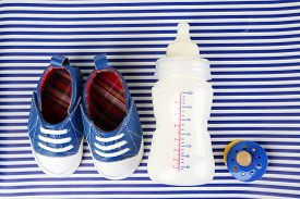 foto of nipples  - Baby shoes with nipple and bottle of milk on blue background - JPG