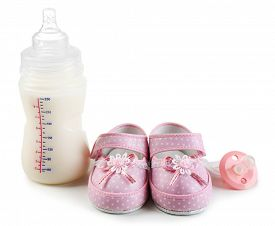 stock photo of nipples  - Baby shoes with nipple and bottle of milk isolated on white - JPG