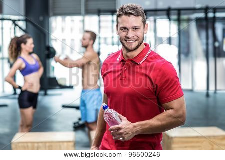 Portrait of muscular trainer with athletes on the background