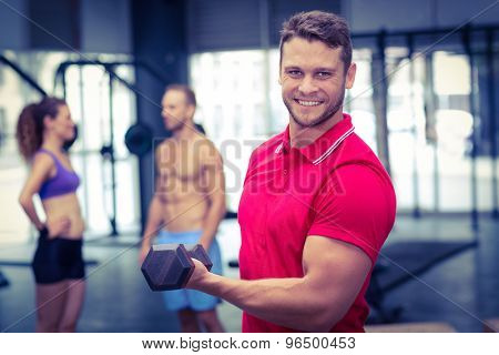 Portrait of a muscular trainer lifting a dumbbell