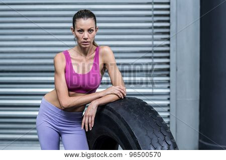 Portrait of a serious muscular woman leaning on a tire