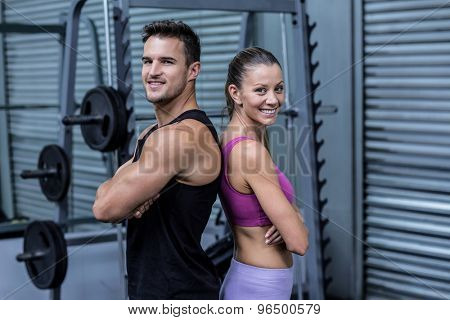 Portrait of a smiling muscular couple giving back to back