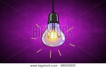 Illuminating hanging light bulb on dark background