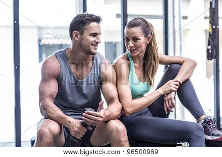 Muscular couple sitting on the bench and discussing together
