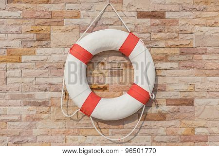 The Life Buoy Is Hanged On Brick Wall Background Nearby The Swimming Pool, For Safety And Rescue.