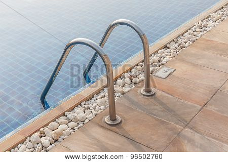 Steel Ladder And Clear Blue Swimming Pool.