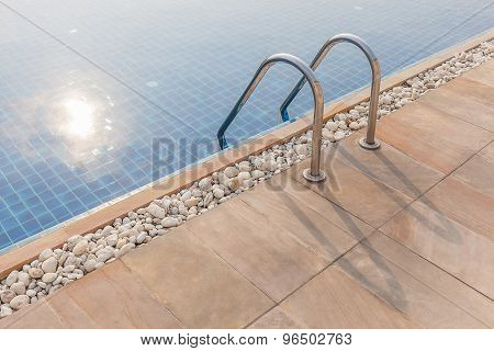 Steel Ladder Of Swimming Pool And Sunlight Reflection In Summer Time.