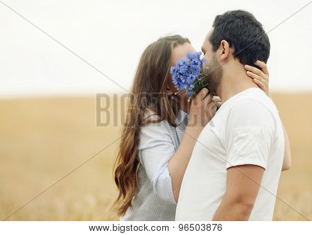 Sensual Young Couple Hiding A Kiss Behindthe Flowers