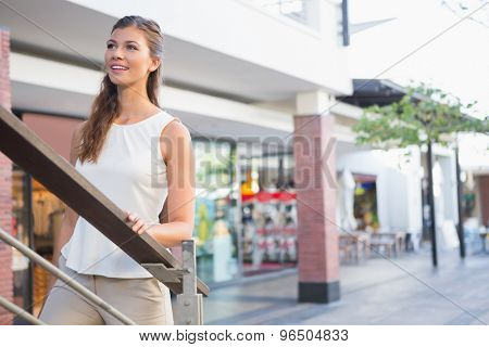 Smiling woman going upstairs at the shopping mall