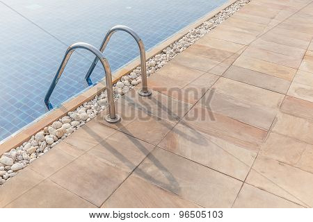 Grab Bars Ladder In The Clear Blue Swimming Pool.