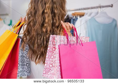 Back view of woman holding shopping bags at a boutique