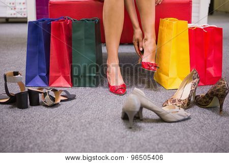 Woman sitting next to shopping bags and putting on shoes at a shoe shop