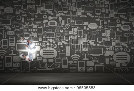 Funny image of jumping businesswoman on background of media icons
