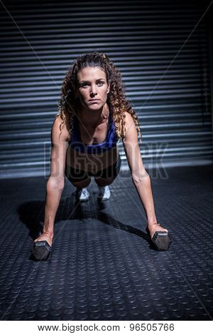 Muscular woman doing push-ups with dumbbells