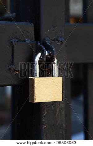 Closeup Brass Padlock On A Black Metal Gate.
