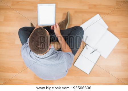 Upward view of young creative businessman working on tablet