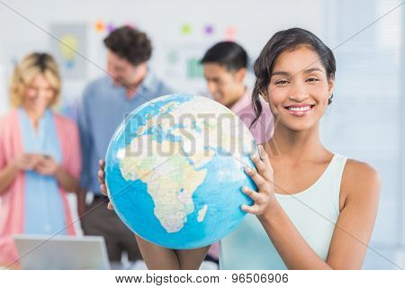 Casual woman holding a globe during a meeting
