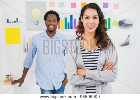 Young smiling business team looking at the camera with the woman in front in the office