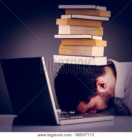 Exhausted businessman sleeping head on laptop against grey vignette