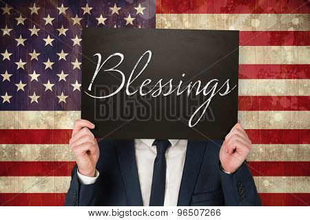 Businessman holding board against usa flag in grunge effect