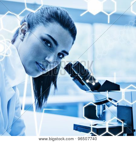 Science graphic against brunette posing with a microscope