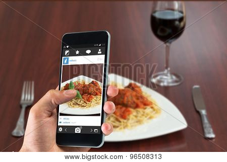 hand holding smartphone against front view of spaghetti and meatballs with red wine