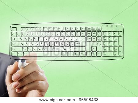Close up of hand darwing computer keyboard with marker