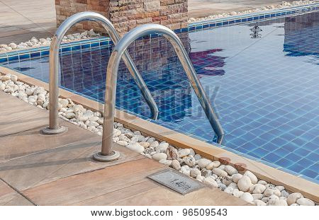 Clear Blue Swimming Pool With Steel Stair In Hotel.