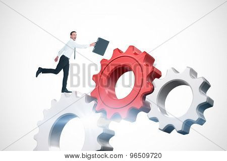 Happy businessman leaping with his briefcase against white and red cogs and wheels