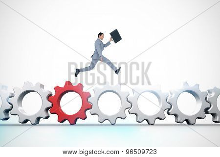 Businessman running with a suitcase against red and white cogs and wheels