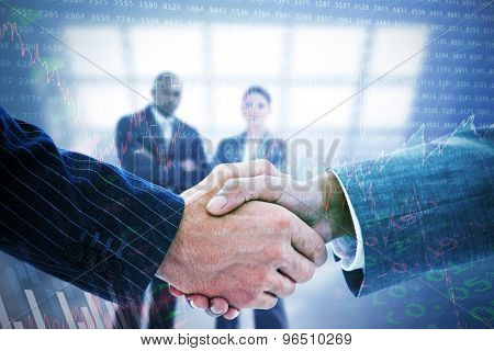 Business people shaking hands against stocks and shares