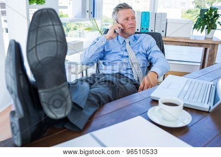 Businessman relaxing in a swivel chair and having a phone call in office