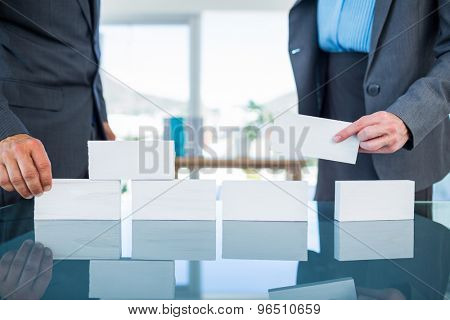 Business people stacking paper bloc in office