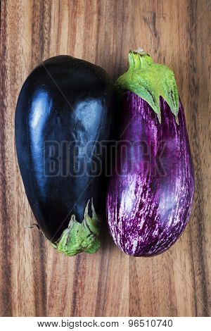 Fresh ripe aubergine and stripped raw eggplants over wood background