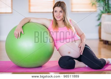 Pregnant woman looking away with exercise ball in the living room