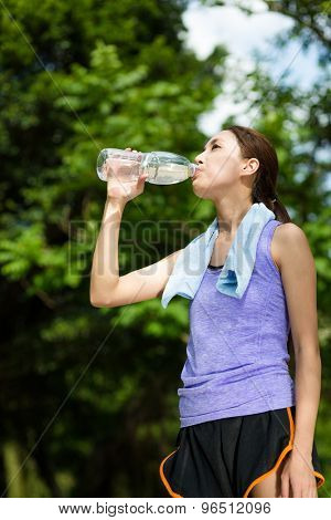 Young female athlete drinking water to refresh