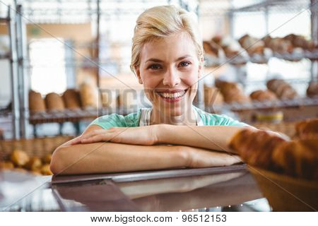 Smiling waitress posing next basket of bread at the bakery