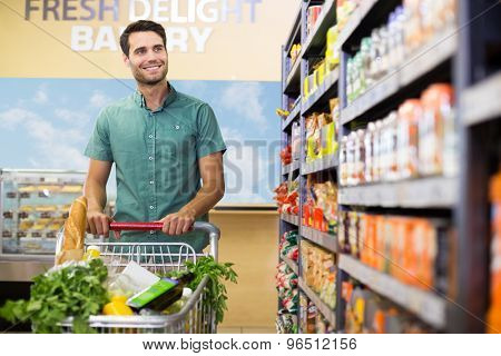 Portrait of smiling man walking in aisle with his trolely at supermarket