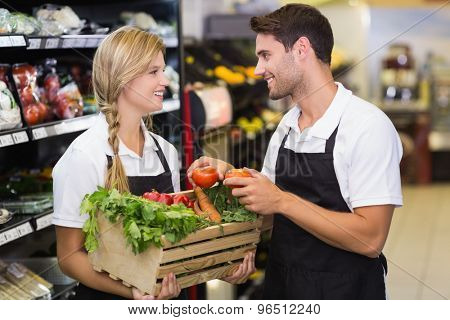 Smiling colleagues holding a box with fresh vegetables at supermarket