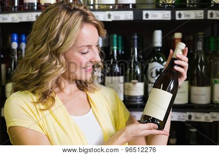Smiling pretty blonde woman showing a winr bottle in supermarket