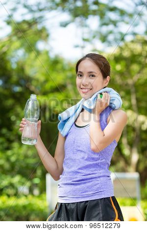 Fitness woman drinking water after running
