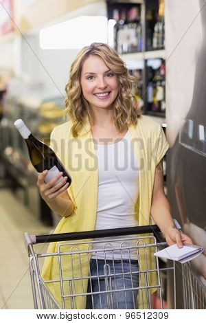 Portrait pf a smiling pretyt blonde woman having a notepad and wine bottle in her hands in supermarket