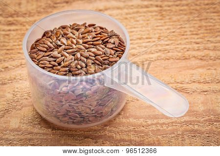 measuring scoop of brown flax seeds against textured cedar wood
